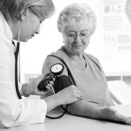 Female doctor measuring blood pressure of senior women