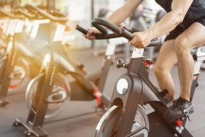 man cycling on bike in gym