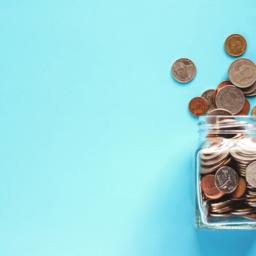 jar of coins on blue background
